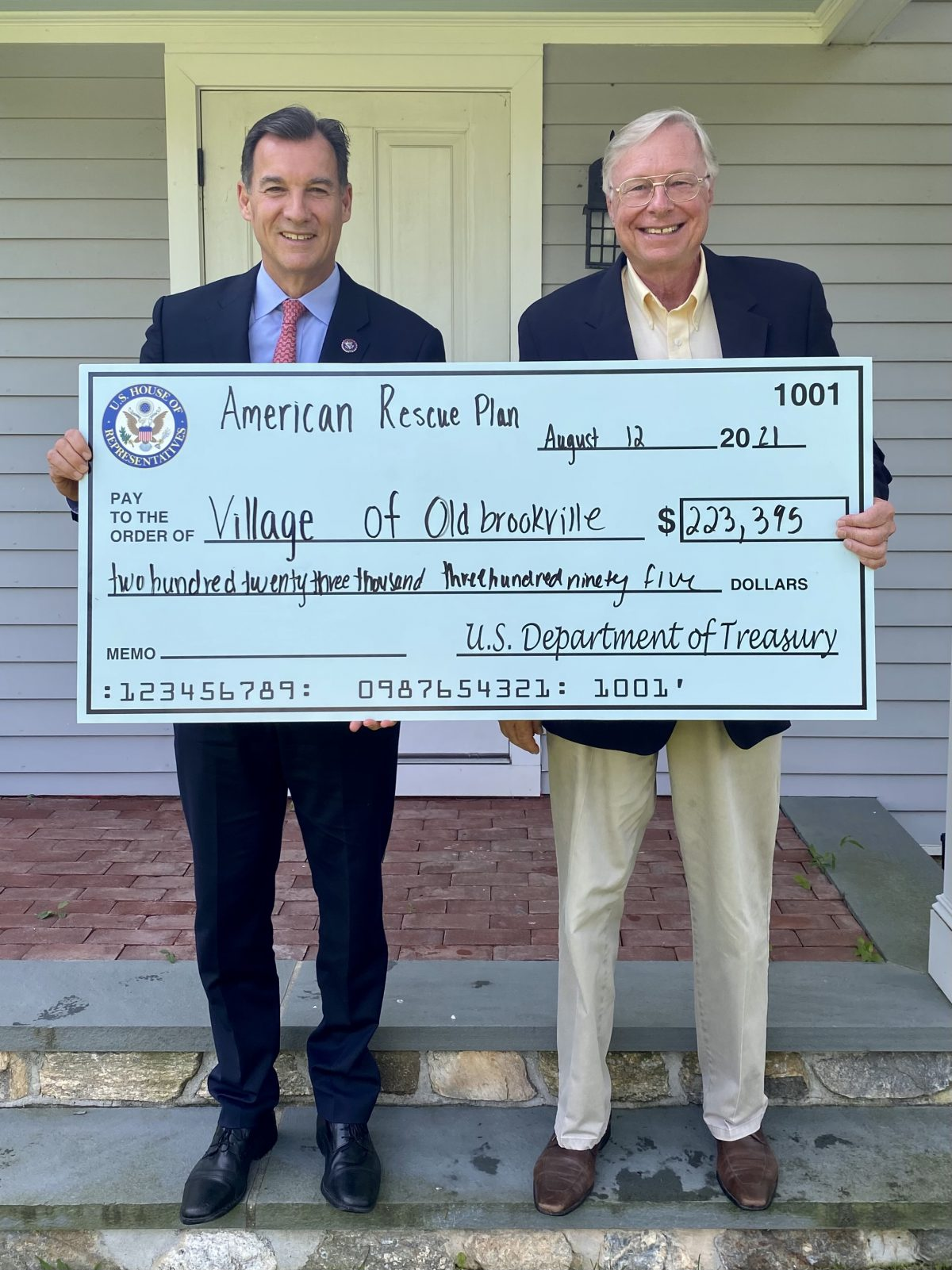 Pictured are United States Congressman Tom Suozzi presenting a mock check to Old Brookville Mayor Bernie Ryba